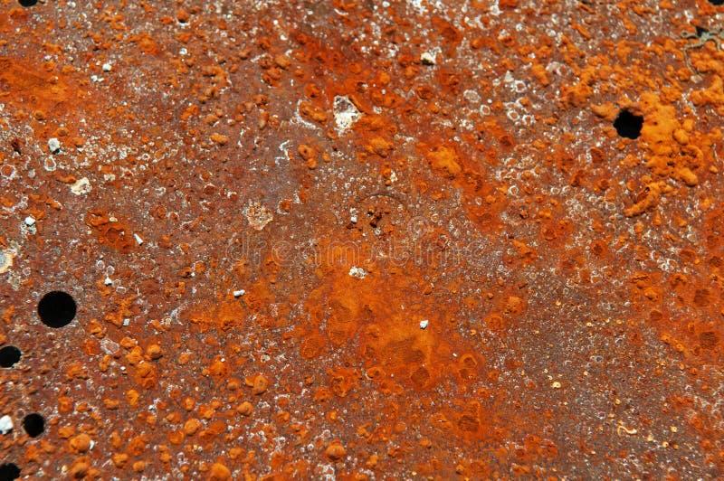 Plaque de métal avec la surface orange rouillée avec des trous photographie stock libre de droits