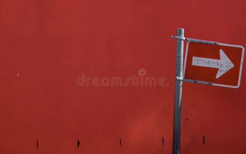 Plaque de rue blanche de flèche sur un fond rouge photo libre de droits