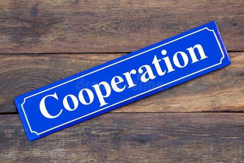 Plaque de rue de coopération sur le fond en bois photos libres de droits