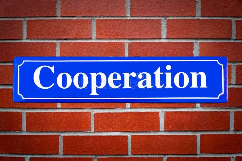 Plaque de rue de coopération sur le mur de briques photo stock
