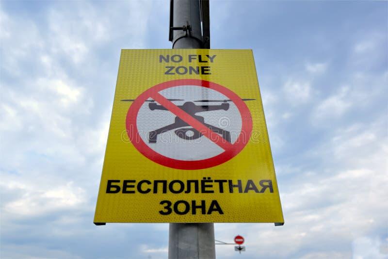 Plaque de rue en anglais et russe : Aucune zone de mouche photographie stock libre de droits