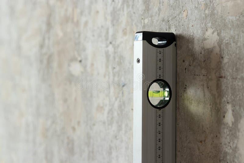 Plaque de séchage et niveau de construction près du mur photographie stock