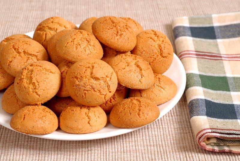 Plaque des biscuits italiens croquants d'Amaretti avec une serviette checkered images stock