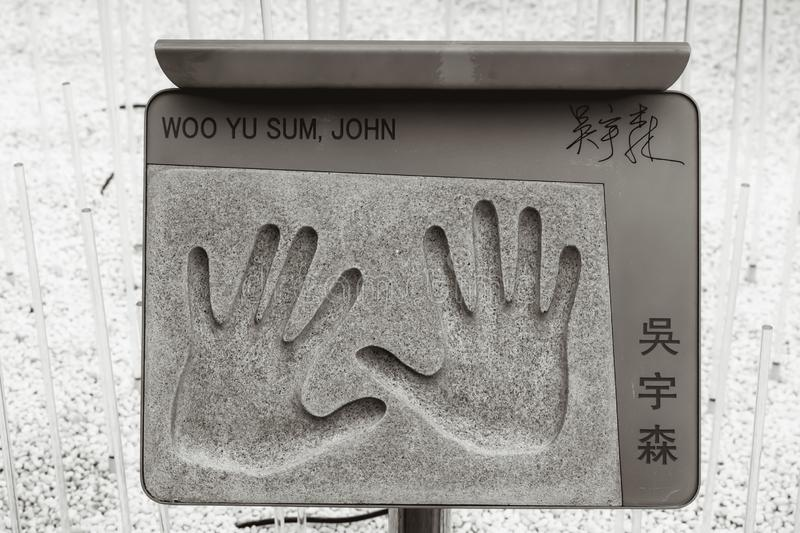 Plaque with the handprint of John Woo in Hong Kong. Plaque with the hand imprint of famous Chinese action movie director John Woo placed in the Garden of Stars stock image