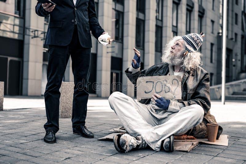 Plaque signalétique de transport de sans-abri supérieur aux cheveux gris et prise de la nourriture de morsure photographie stock libre de droits