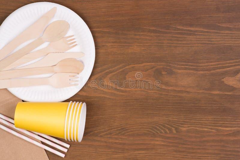 Plaques à papier et tasses jetables et couverts en bois sur la table en bois avec l'espace de copie photographie stock libre de droits