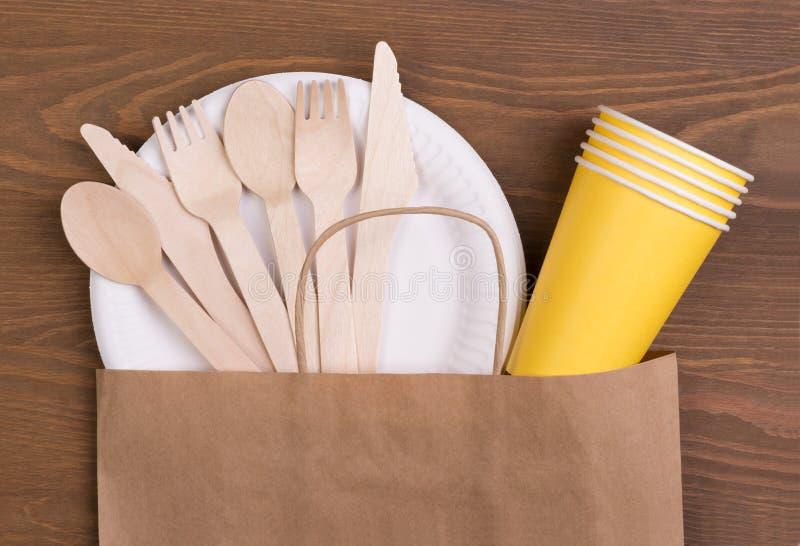 Plaques à papier et tasses jetables et couverts en bois sur la table en bois dans un sac de papier image libre de droits