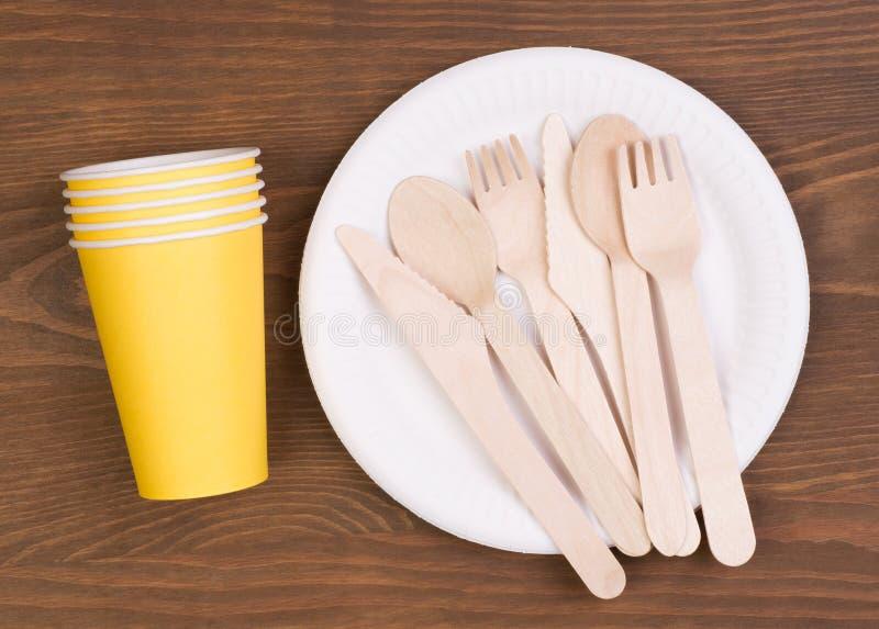 Plaques à papier et tasses jetables et couverts en bois sur la table en bois images stock
