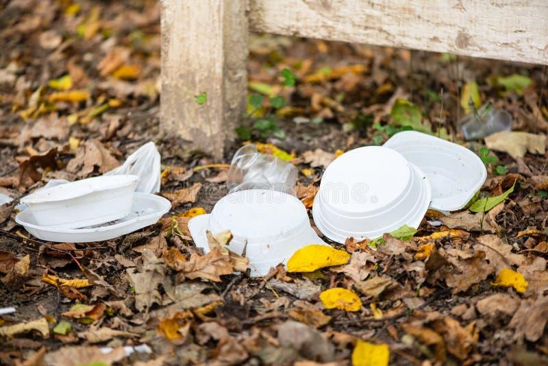 Plaques, tasses et sacs en plastique jetables sur le sol dans la forêt Idée de la contamination de la nature par les peuples, imp images libres de droits