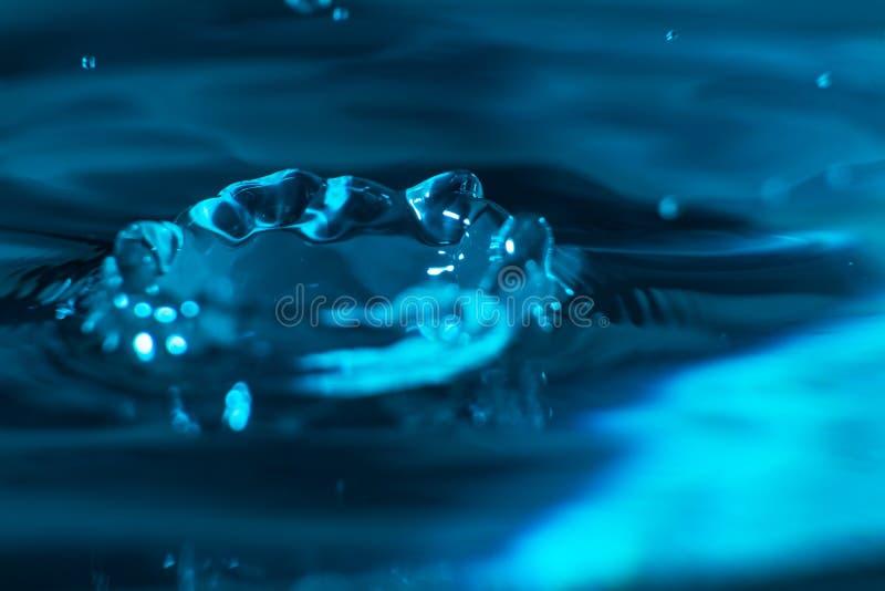 Plaska av en droppe av vatten, när du faller på kristallklart vatten Lokalvård- och renhetbegrepp Makro av vatten i rörelse arkivbild