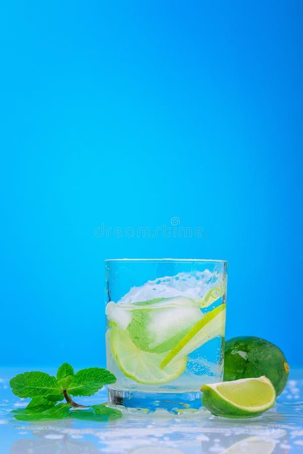 Plaska mojitococtailen med limefrukt och den nya mintkaramellen i exponeringsglas på en blå bakgrund arkivfoton