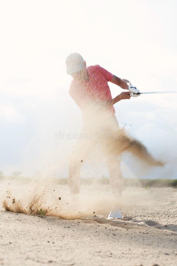 Plaskande sand för medelålders man, medan spela på golfbanan arkivbild