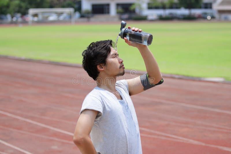 Plaskande vatten för stilig ung asiatisk konditionman på hans framsida efter inkört spår av stadion royaltyfri fotografi