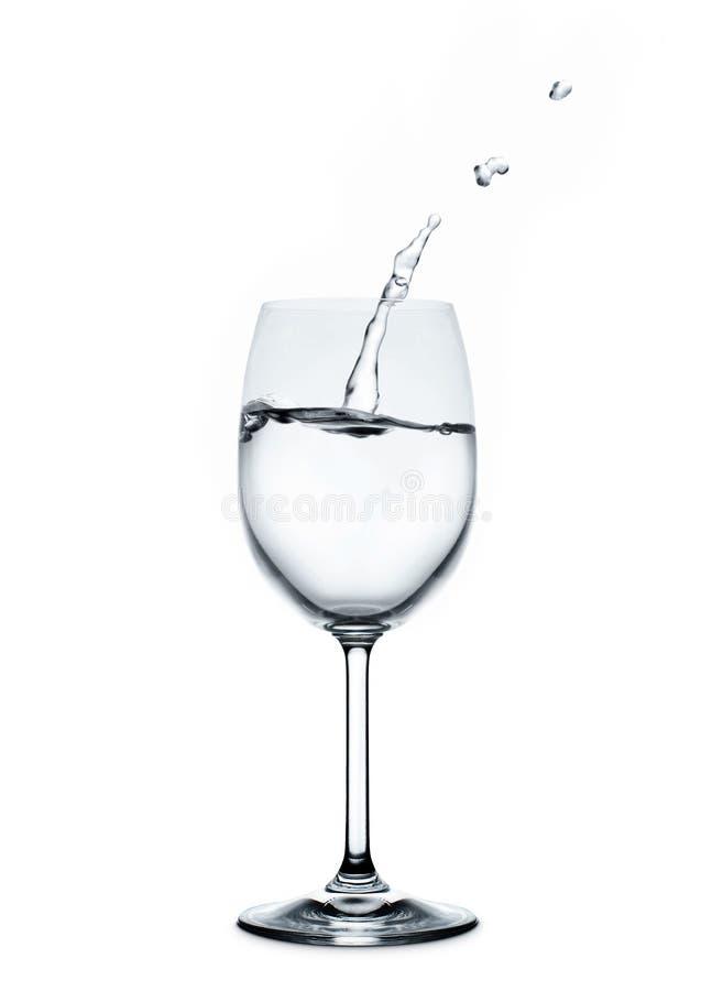 Plaskande vattenvåg i vinexponeringsglaset arkivfoton