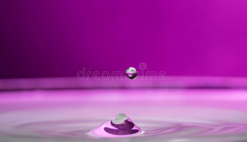 Plaskat ut och plaskat från en fallande droppe på en kulör eller svart bakgrund arkivfoto