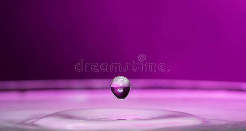 Plaskat ut och plaskat från en fallande droppe på en kulör eller svart bakgrund royaltyfri fotografi