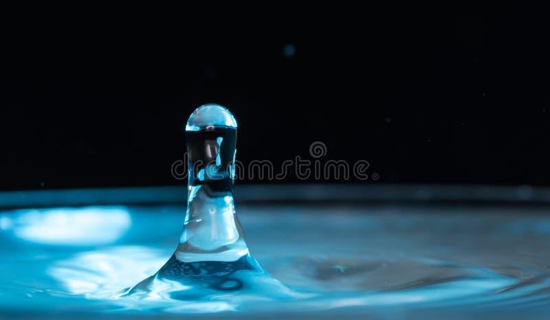 Plaskat ut och plaskat från en fallande droppe på en kulör eller svart bakgrund arkivbild