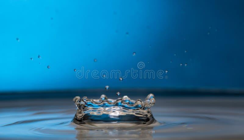 Plaskat ut och plaskat från en fallande droppe på en kulör eller svart bakgrund royaltyfri foto