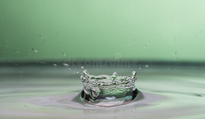 Plaskat ut och plaskat från en fallande droppe på en kulör eller svart bakgrund arkivfoton