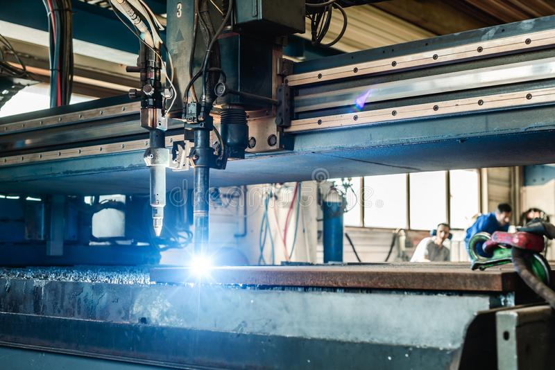 Plasma cutter in a factory cutting piece of metal stock image