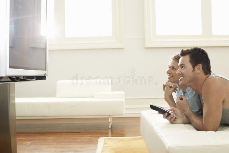 Plasma De Observación TV De Los Pares En Casa Imágenes de archivo libres de regalías