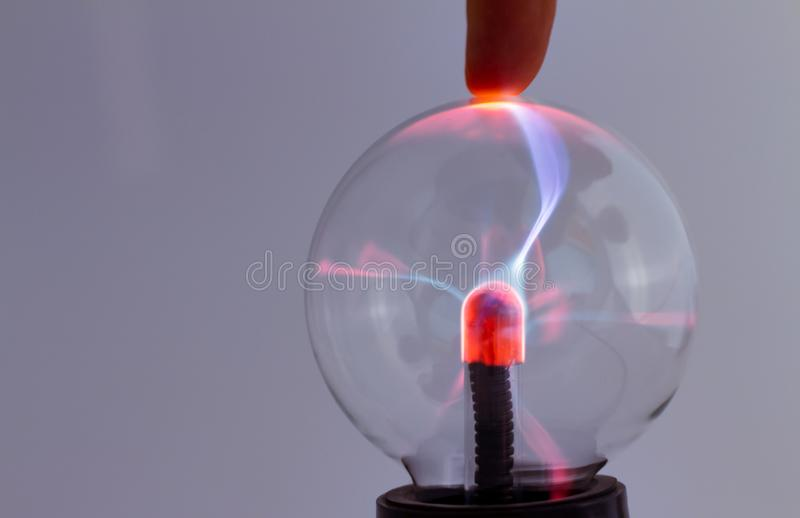 Plasma lamp on neutral background. Fingers of a man attracting the luminous electric flow. Crystal ball with electricity and light. Electricity made light stock photo
