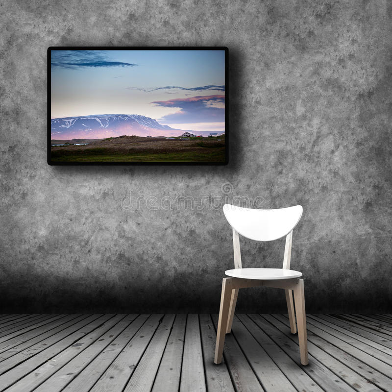 Plasma TV on the wall of the room with empty chair stock image