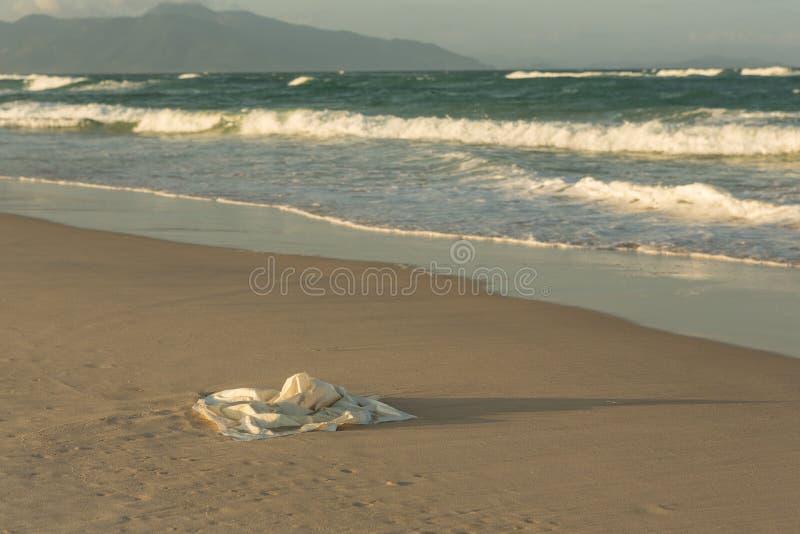 Plast- avskräde på stranden i havet, plastpåse förorenar havet och naturen royaltyfria foton