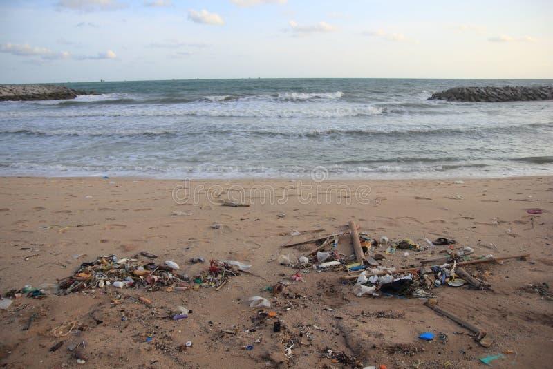 Plast- avskräde, skum, och smutsar ner avfalls på stranden i sommardag royaltyfri bild