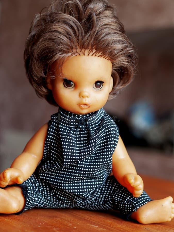 Plast- barn danar dockan i kläder från berömda formgivare fotografering för bildbyråer