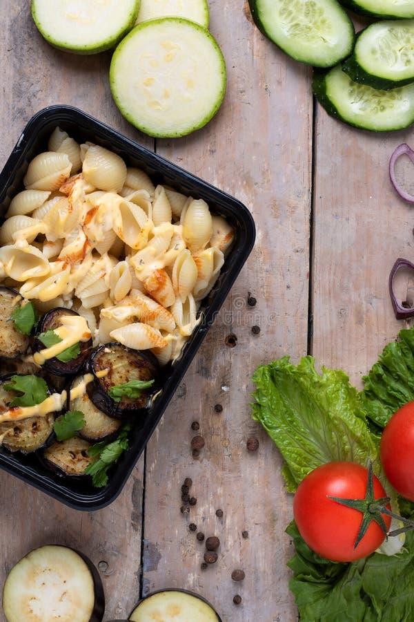 Plast- behållare med grillade fega vingar och rå grönsaker på lantlig bakgrund, grönsaksallad royaltyfri bild