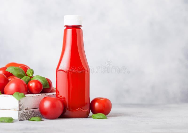 Plast- behållare med sås för tomatketchup med rå tomater på kökstenbakgrund royaltyfri bild
