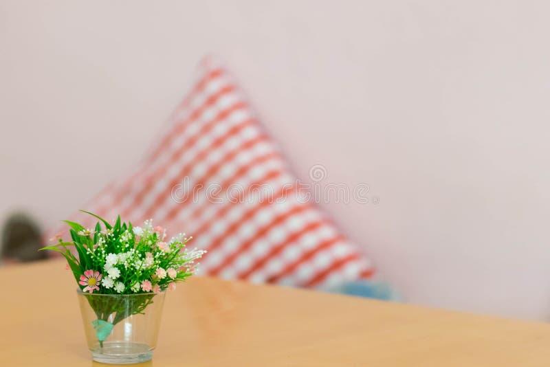 Plast- blommor i den glass vasen på tabellen med suddighet kudde backgrpo royaltyfria foton