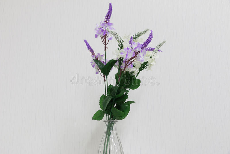 Plast- blommor i en vas på ett mörker - grå bakgrund royaltyfri foto