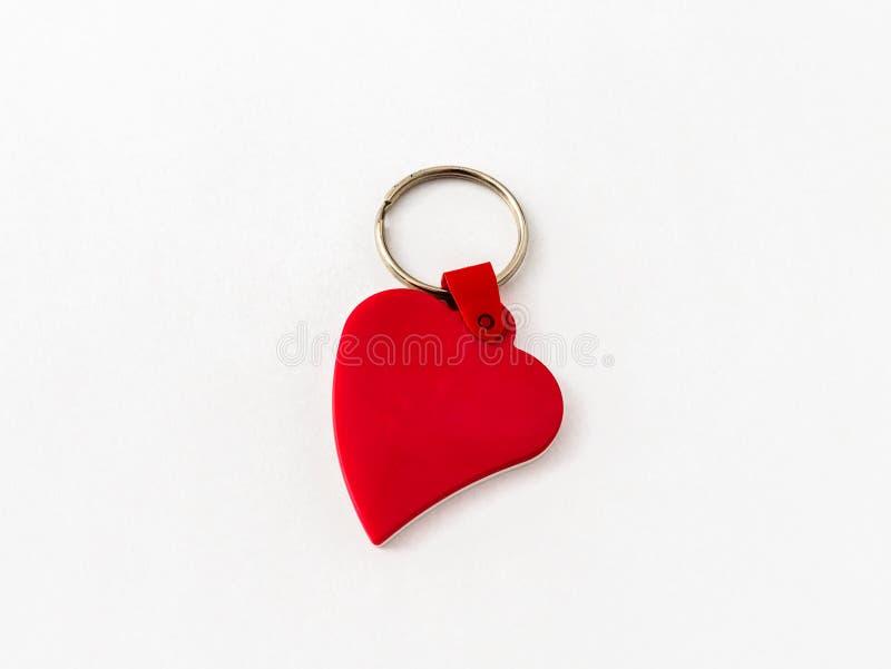 Plast- breloque för nyckel- cirkel i formen av en röd hjärta på en vit bakgrund arkivbilder
