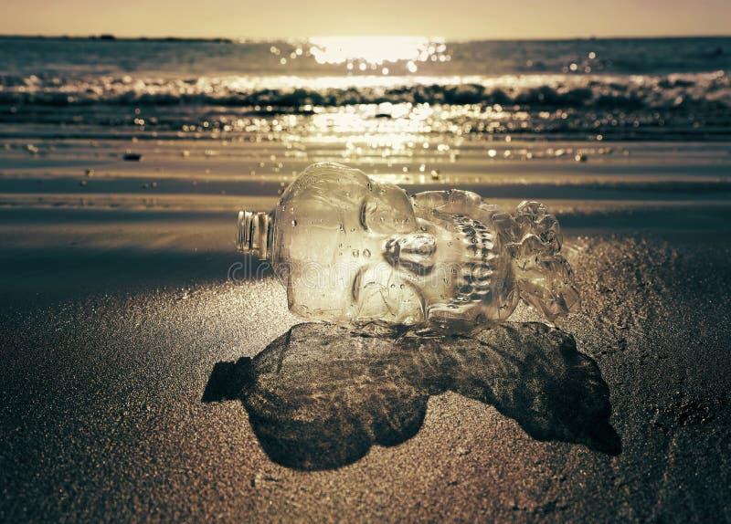 Plast- buteljera på stranden royaltyfri fotografi
