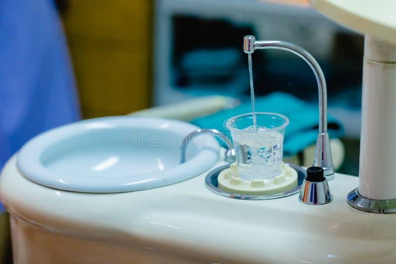 Plast- exponeringsglas med vatten för gemensam operation för tandläkare av cleanin royaltyfria bilder