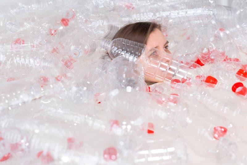 Plast- f?roreningproblem och milj?skydd Svag tr?tt kvinna i en h?g av plast- flaskor R?ddningjordbegrepp arkivbild