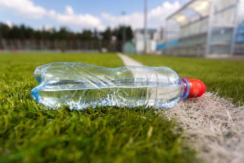 Plast- flaska av vatten som ligger på gräsfotbollfält arkivfoto