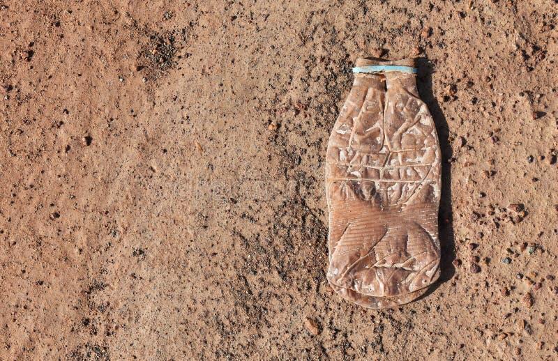 Plast- flaska och liten sten på jordning för torr jord arkivbild