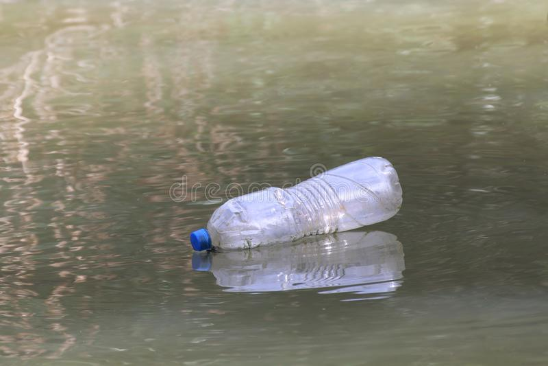 Plast- flaskavfalls på den smutsiga vattenyttersidan, ruttet vatten, flaskavfalls arkivbilder