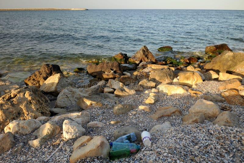 Plast- flaskor av vatten på kusten som förorenar miljön arkivfoto