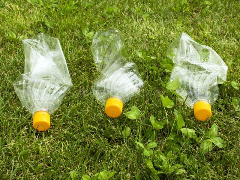 Plast- flaskor ligger på det gröna gräset F?rorening av naturen Racka ner på på gräsmattan fotografering för bildbyråer