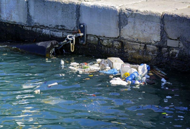 Plast- flaskor och annat avfall på havsport royaltyfria bilder