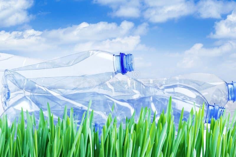Plast-flaskor p? gr?nt gr?s Milj?belastningbegrepp ekologi royaltyfri fotografi