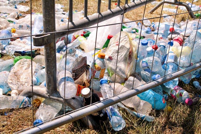 Plast- flaskor som kastas av metallstaketet Använda tomma husdjurflaskor som bort kastas och lämnas på gräs efter ett parti för ö royaltyfri bild