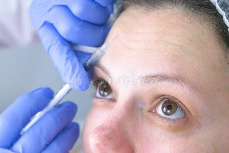 Plast- framsida för kontur Föryngra det ansikts- injektiontillvägagångssättet för att dra åt och att släta skrynklor på framsidah royaltyfri foto