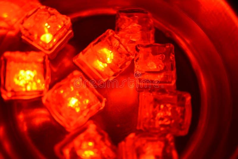 Plast- glödande ljusa röda iskuber i vatten Röda isisflak svävar i en rostfritt stålskopa med en beträffande intressant metall arkivfoton