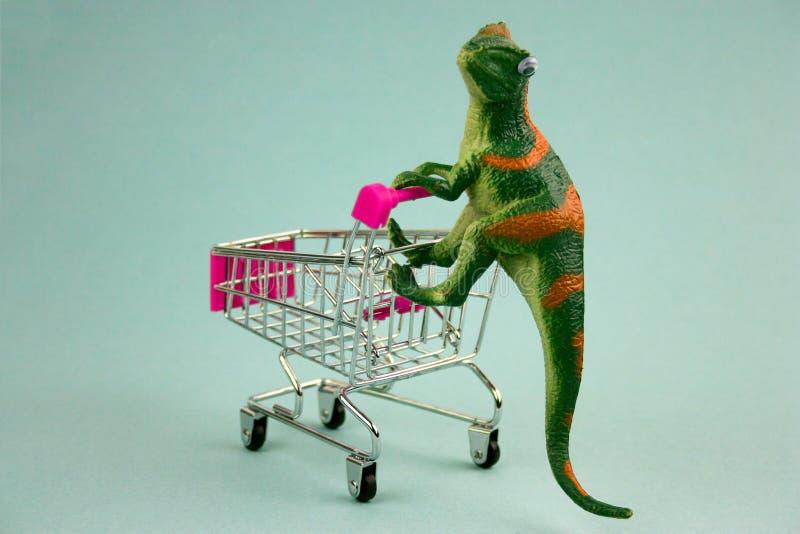 Plast- grön dinosaurie med shoppingvagnen fotografering för bildbyråer