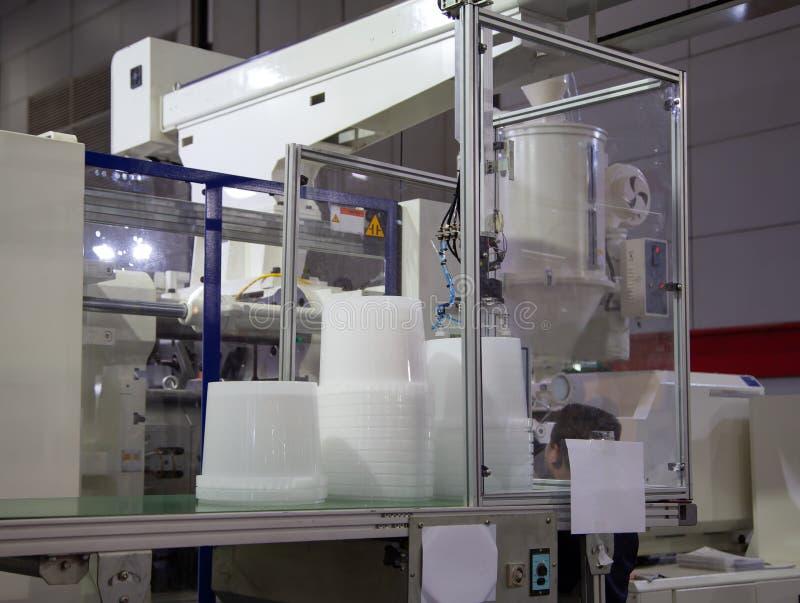 Plast- hinkar från maskinen för press för injektionstöpning arkivbilder